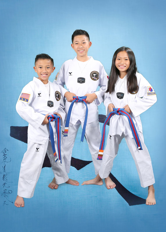 three young kids holding on their striped belts