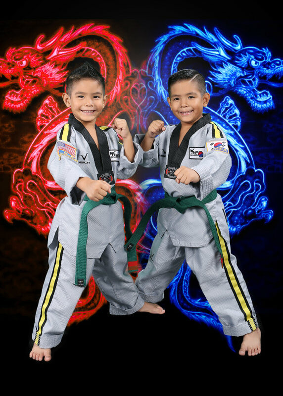 two kids posing in their taekwondo fighting stance with a red and blue dragon in the background