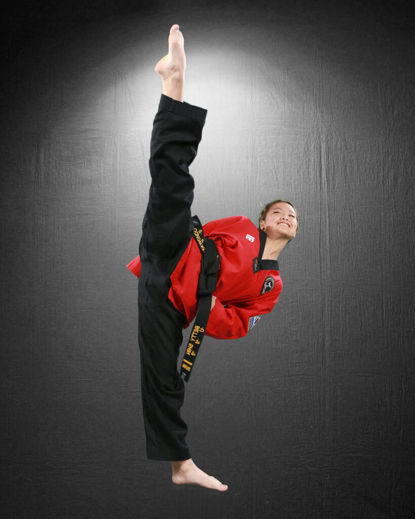 woman smiling kicking her leg up while wearing a taekwondo uniform