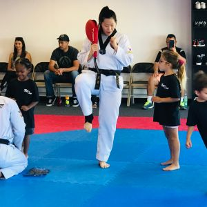 Woman wearing taekwondo uniform teaching a student about form