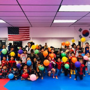 group photo of kids holding balloons wearing super hero costumes