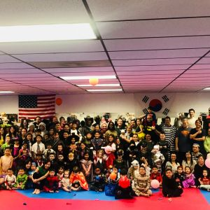 group photo of kids and adults wearing various types of halloween costumes
